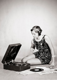 蓄音機のレコードを聞いている女の子。ビンテージ