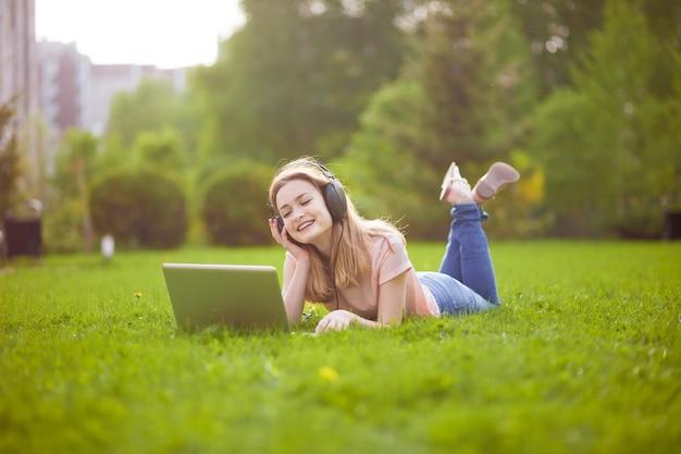公園でノートパソコンから音楽を聴いている女の子