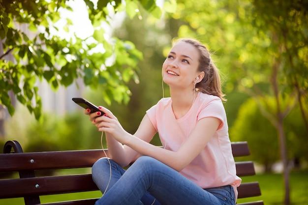 ベンチで公園で携帯電話から音楽を聴いている女の子