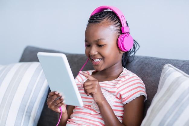 デジタルタブレットから音楽を聴いている女の子