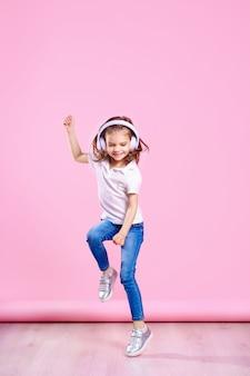 ピンクの壁にヘッドフォンで音楽を聴いている女の子。踊る少女。音楽に合わせて踊る幸せな小さな女の子。幸せなダンス音楽を楽しんでいるかわいい子。