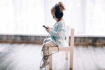 Girl listening to music on chair