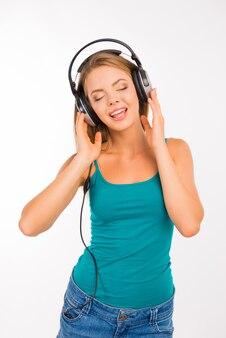 헤드폰에서 음악을 듣고 노래하는 소녀