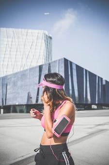 Девушка слушает музыку на повязке с сенсорным экраном и наушниками в барселоне