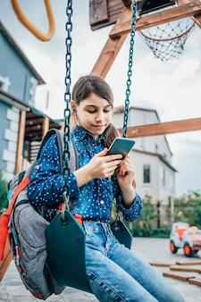 後ろにバックパックを背負ってブランコに座って携帯電話で音楽を聴いている女の子。