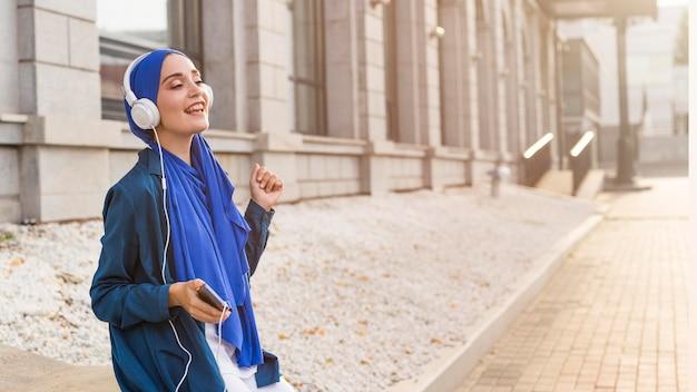 コピースペースと屋外のヘッドフォンで音楽を聴いている女の子