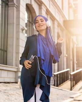 外のヘッドフォンで音楽を聴いている女の子