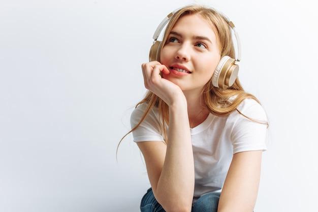 큰 헤드폰을 통해 음악을 듣고 랩톱에 앉아 소녀