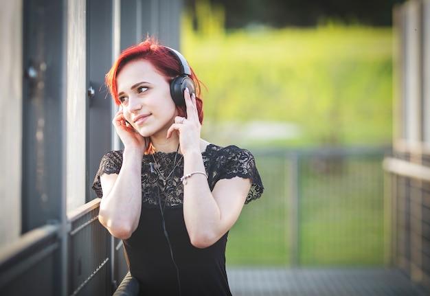 Девушка слушает музыку через наушники на улице.