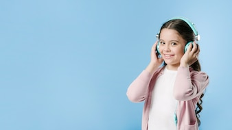 Girl listening to music with headphones in studio