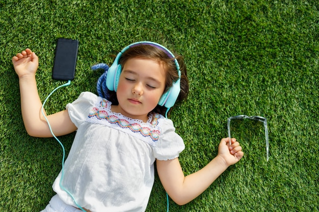 Девушка слушает музыку с наушниками, лежа на траве с закрытыми глазами