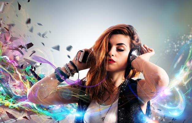明るい色の縞でヘッドフォンで音楽を聴いている女の子
