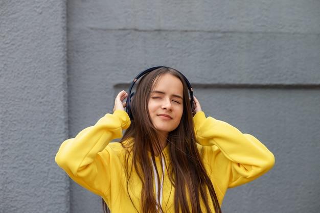 路上でヘッドフォンで音楽を聴いて、踊って、灰色で楽しんでいる女の子