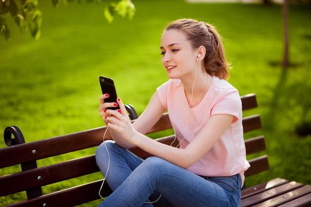 公園で携帯電話で音楽を聴いている女の子