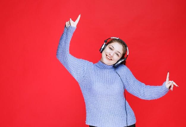 Девушка слушает музыку в наушниках и веселится.
