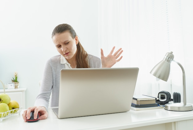 Girl listens or looks at information on computer with disbelief. skeptical expression.