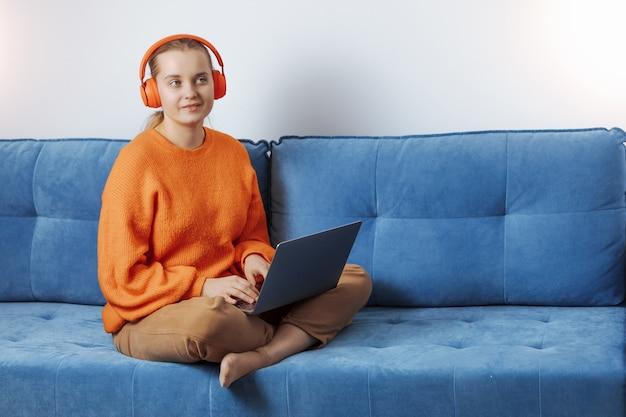 女の子はコンピューターでヘッドフォンで音楽を聴きます