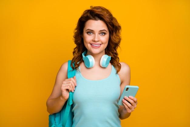 소녀는 헤드폰에서 음악을 듣고 전화를 사용