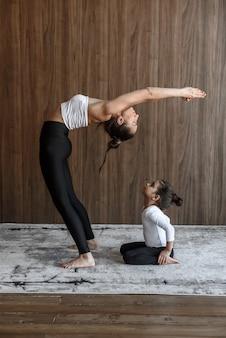 Девушка маленький ребенок смотрит, как мама занимается спортом, занимается йогой и растяжкой