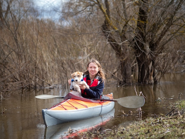 A girl and a little puppy are sailing on a kayak .