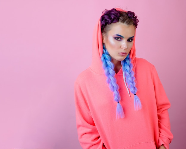 Girl long braids pink background isolated. keep hairstyle braided for healthier hair. hairdresser salon. kanekalon strand in braids.