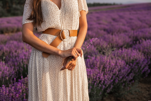 A girl in a long dress holding a sprig of lavender