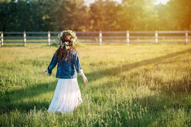 A girl in a long dress and a wreath of fresh wildflowers in a field in the morning at sunrise. horizontal