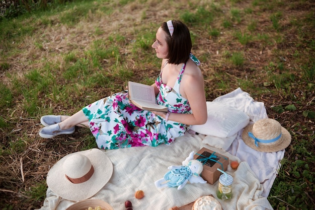 A girl in a long summer dress with short hair sits on a white blanket with fruits and pastries, straw hats and read a book in a city park