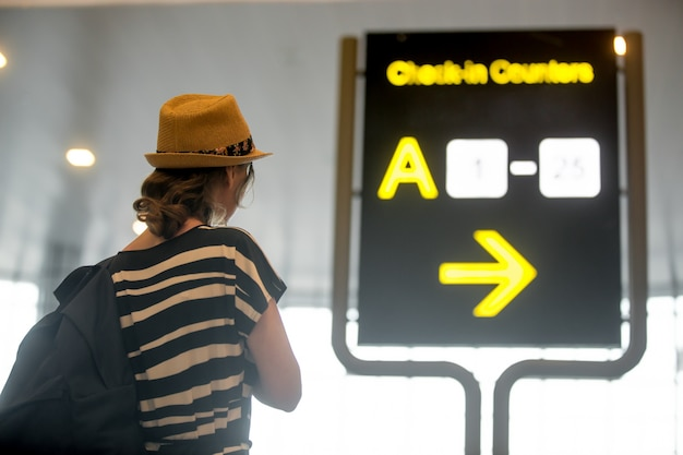 Girl looking at airport information board