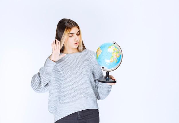 Девушка смотрит на земной шар и пытается найти над ним места.