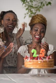 Девушка, глядя на торт ко дню рождения в окружении друзей