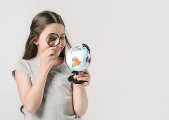 Girl looking at globe with loupe