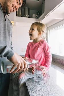 Девушка, глядя на своего отца, наливая воду в стекло
