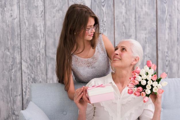 Девушка смотрит на свою бабушку, держит в руках подарочную коробку и букет цветов тюльпана