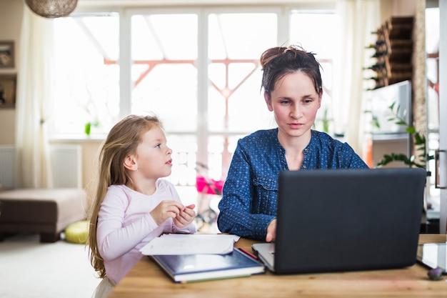 나무 책상 위에 노트북에서 일하는 그녀의 어머니를보고 소녀