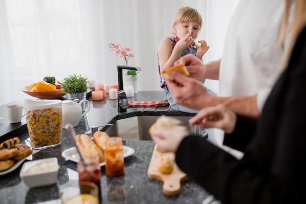 サンドイッチを準備している両親を見ている少女