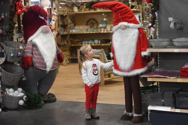 장난감과 장식이 있는 가게에서 산타클로스를 바라보는 소녀