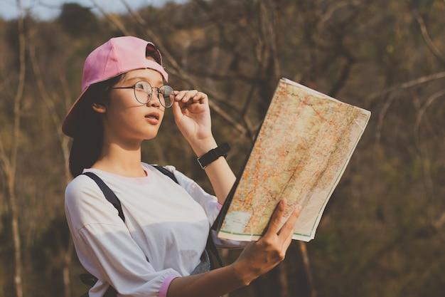 地図を見ている少女は休暇中に森林を旅行します。