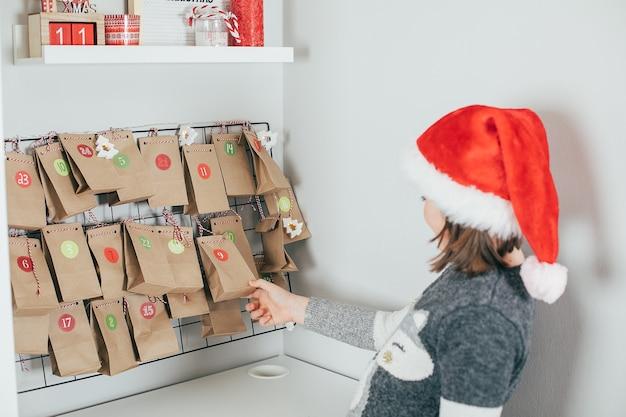 クリスマスのアドベントカレンダーを探している女の子。クリスマスの帽子をかぶった子供が贈り物を開きます。休日のコンセプト