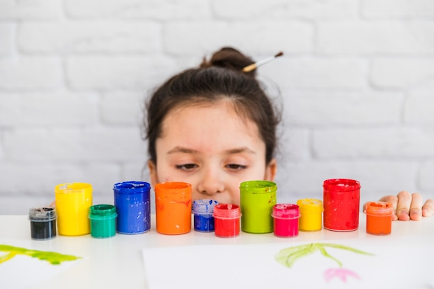 Girl looking at colorful paint bottles at the edge of white table