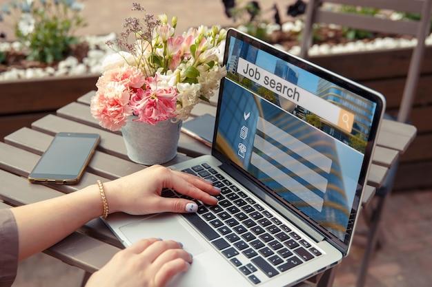 Девушка ищет работу на ноутбуке, сидя за столиком в летнем кафе