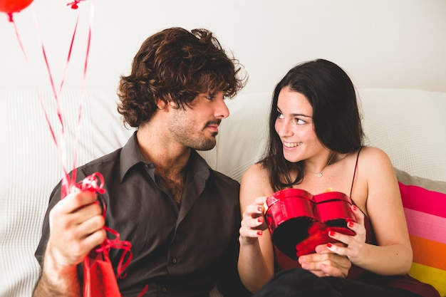 Girl looking at her boyfriend while opening a box of chocolates