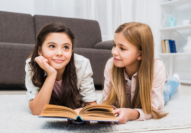 Girl looking at her thoughtful friend while reading book in the living room