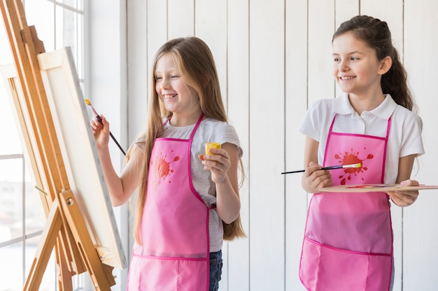 Girl looking at his friend painting on the canvas with paintbrush