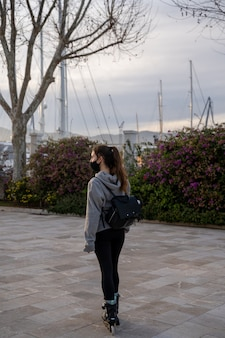 Girl looking at the horizon with skates on the seafront promenade in palma de mallorca, spain