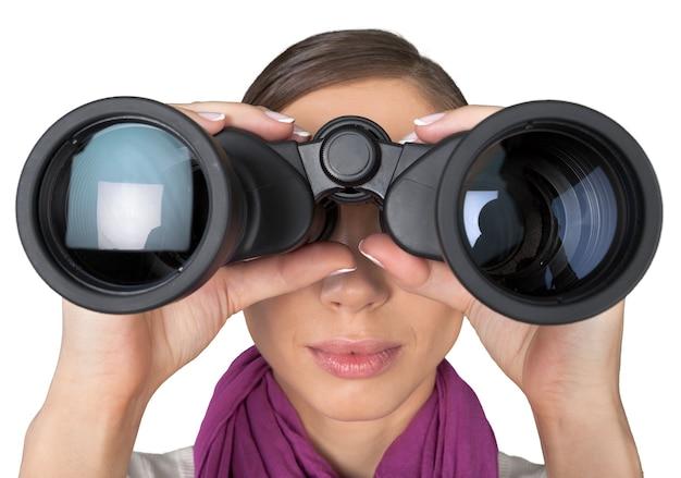 明るい背景で双眼鏡を探している女の子