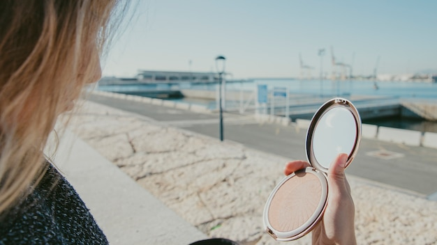 Girl looking into small mirror