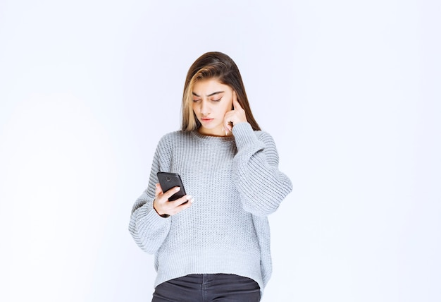 Girl looking to the messages or comments at her smartphone.