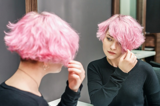 Girl looking in the mirror at her new hairstyle
