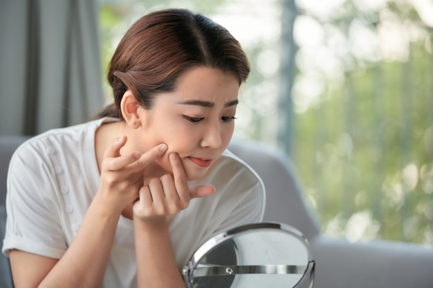Girl looking at mirror and popping a pimple at home.
